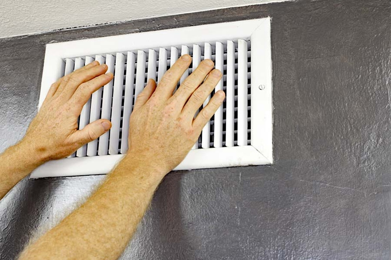 two hands in front of air vent on black wall