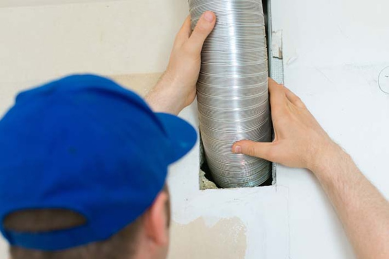 Man setting up ventilation system indoors. When Is It Time for a Split-System AC Replacement?