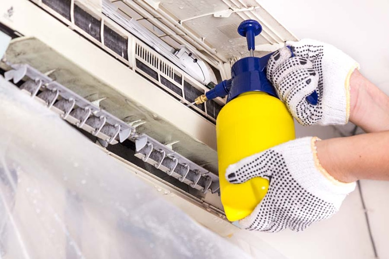 AC Maintenance Checklist, Technician spraying chemical water onto air conditioner coil to clean and disinfect