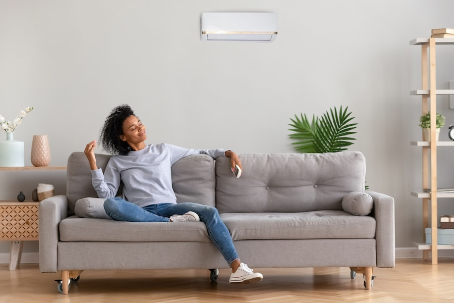 African young relaxed woman sitting on couch breathing fresh air What Accessories Can Help With My Indoor Air Quality?